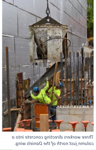 Three workers wearing bright yellow shirts move concrete into a column where it pours down a piece of metal.