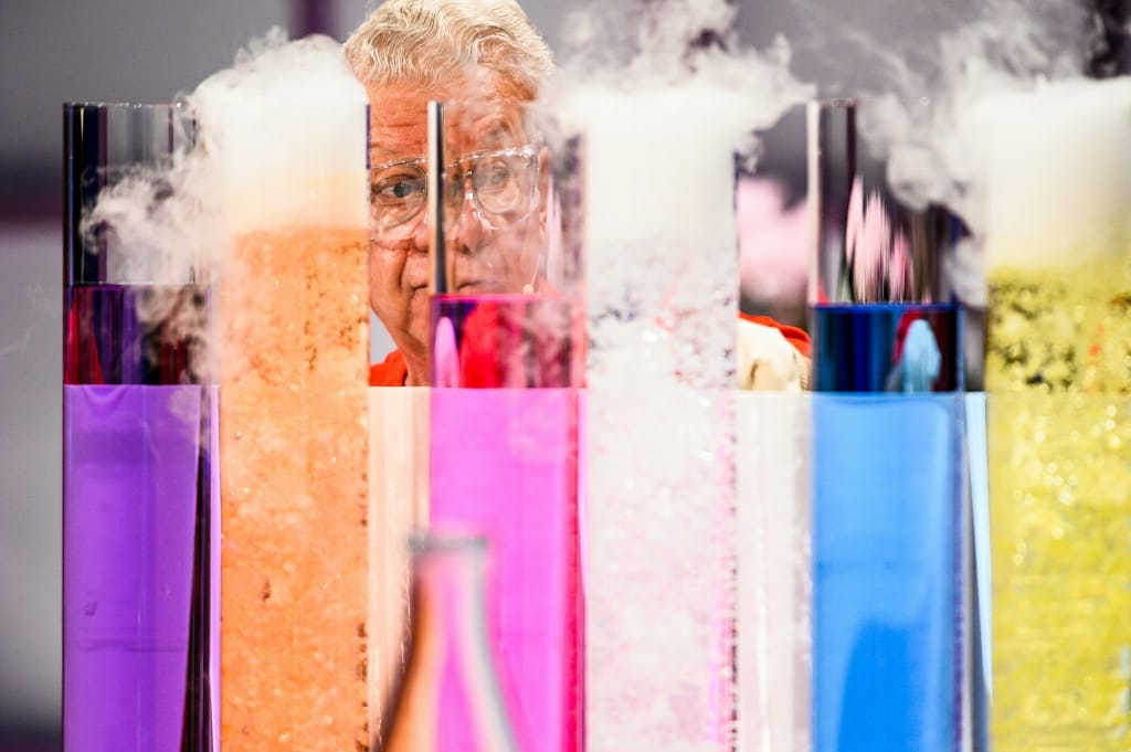 Photo of Shakhashiri seen through brightly colored cylinders of chemicals.
