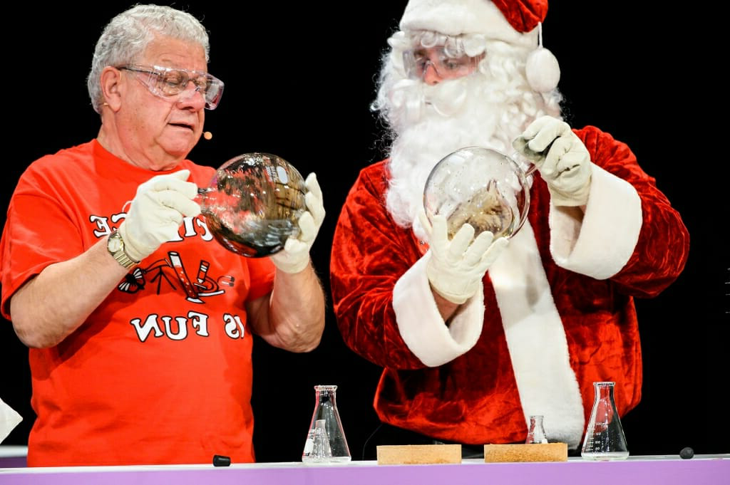 Photo of Santa Claus and Shakhashiri shaking round flasks full of chemicals.