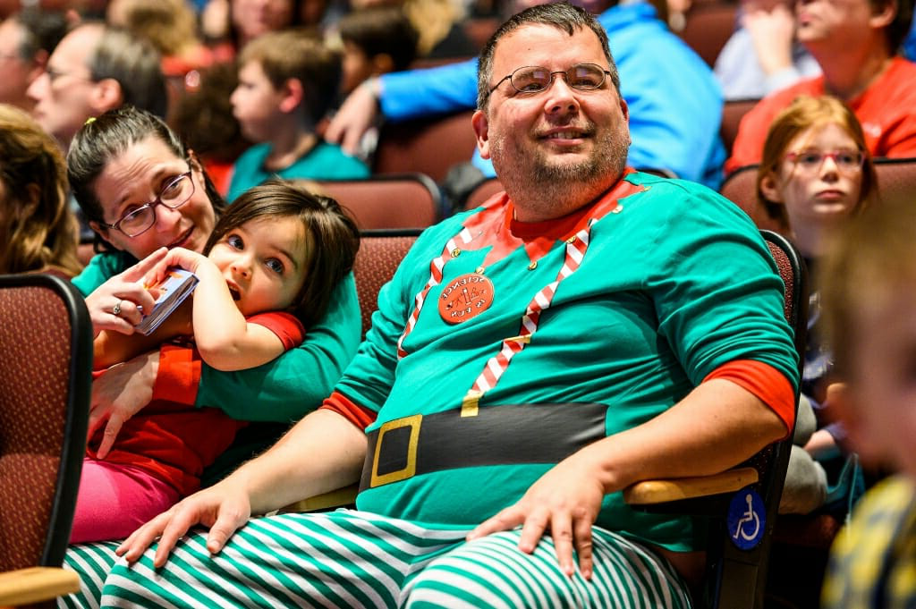 Photo of a father, mother and daughter in red and green elf costumes.