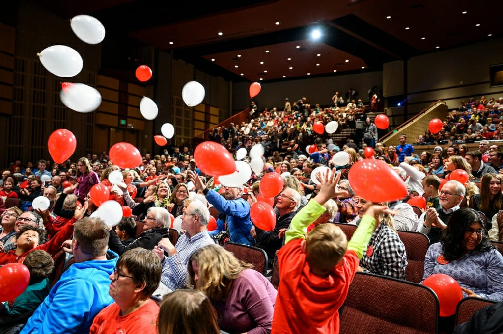 Photo of red and white balloons dropping into the audience.