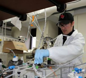 Sean Staudt, a graduate student who works with CA冰, adjusts the flow of dinitrogen pentoxide to a mass spectrometer used to study reactions of the atmospheric gas at atmospheric interfaces.