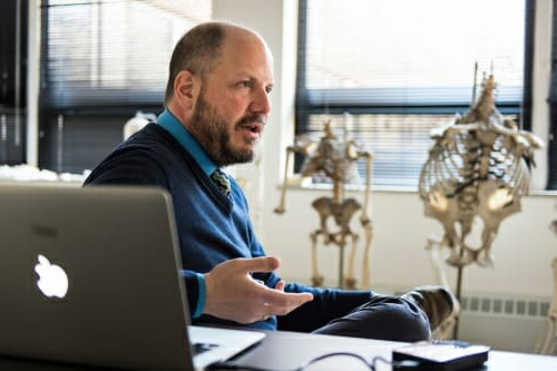 John Hawks sitting at his desk with a laptop open and hominid skeletons in background